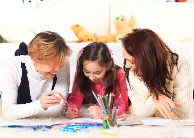 Linda garota desenha com sua mãe e tia.
