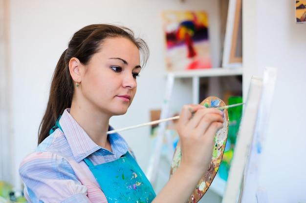 Linda garota desenha uma pintura de pinturas na aula de arte.