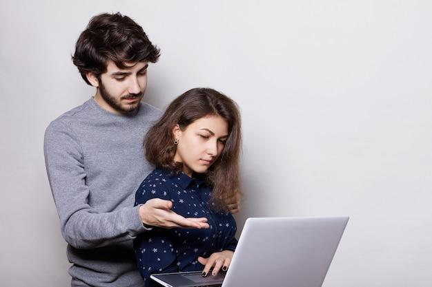 Linda garota, desfrutando de tecnologias modernas, usando seu laptop para escrever seu papel de diploma. estudante barbudo elegante tentando ajudar sua amiga apontando com o braço para a tela.