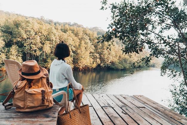Linda garota desfrutar com a natureza, descansando e olhando para o rio.