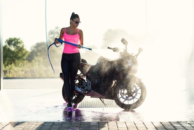 Linda garota deslumbrante lava uma motocicleta no lava-rápido self-service com jato de água de alta pressão