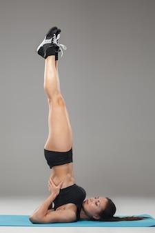 Linda garota desportiva em pé em pose de acrobata ou yoga asana