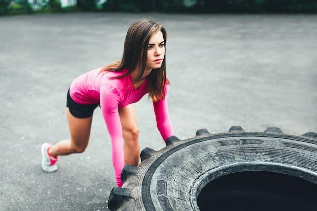 Linda garota desportiva levantando enorme pneu ao ar livre