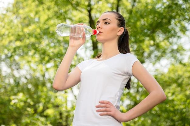 Linda garota desportiva na água potável de t-shirt branca.