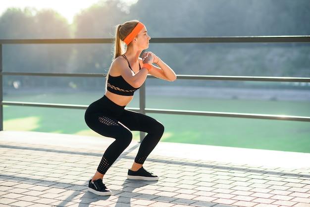 Linda garota desportiva no sportswear preto e bandana laranja que squating durante o treinamento da aptidão no estádio ao ar livre.