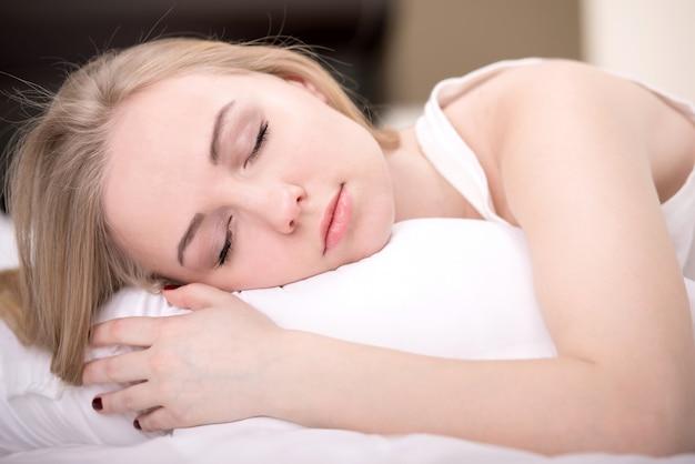 Linda garota dorme no quarto.