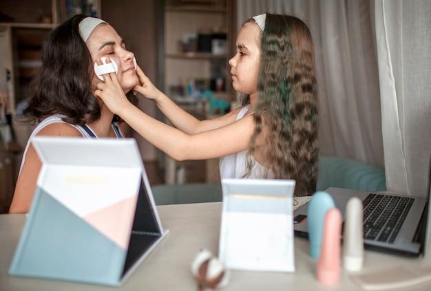 Linda garota e a mãe dela assistindo aula de beleza com tablets online e fazendo procedimentos de spa sozinhas, mãe e filha se divertindo com máscara lisa no rosto, salão de beleza em casa