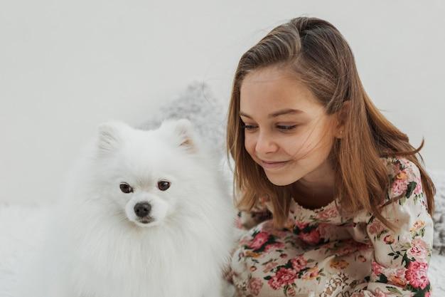 Linda garota e cachorro dentro de casa