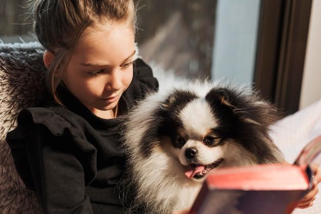 Linda garota e cachorro lendo