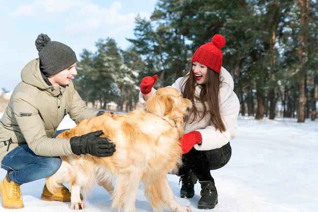 Linda garota e cara plaing com cachorro dourado em um dia ensolarado de inverno na floresta.