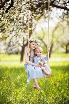 Linda garota e garoto se divertindo em um balanço no florescimento antigo jardim de macieira. dia ensolarado. atividades ao ar livre de primavera para crianças