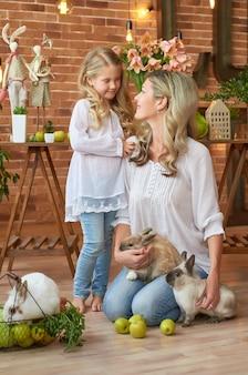 Linda garota e mãe brincando com coelhos