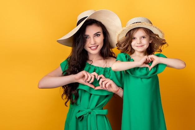 Linda garota e mãe de mãos dadas em forma de coração