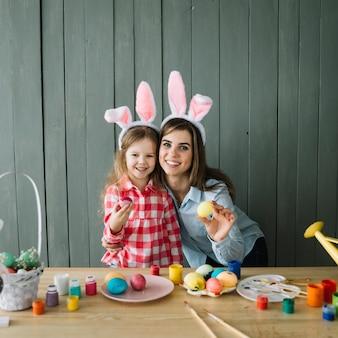 Linda garota e mãe em orelhas de coelho em pé com ovos coloridos