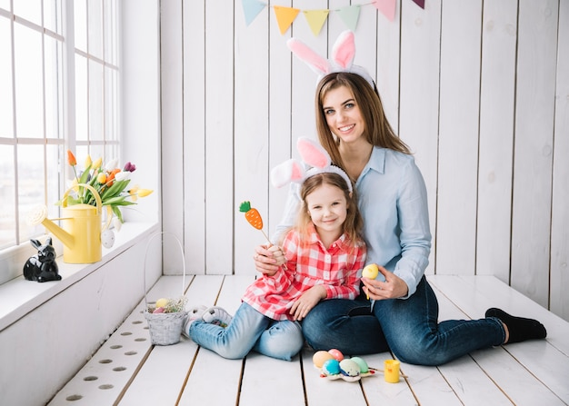 Linda garota e mãe em orelhas de coelho sentado com ovos de páscoa