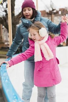 Linda garota e mãe patinação no gelo