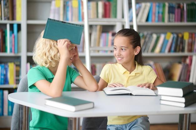 Linda garota e seu amigo alegre sentado em uma biblioteca