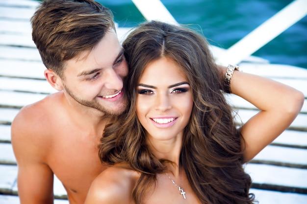 Linda garota e seu namorado descansam na praia perto do mar negro