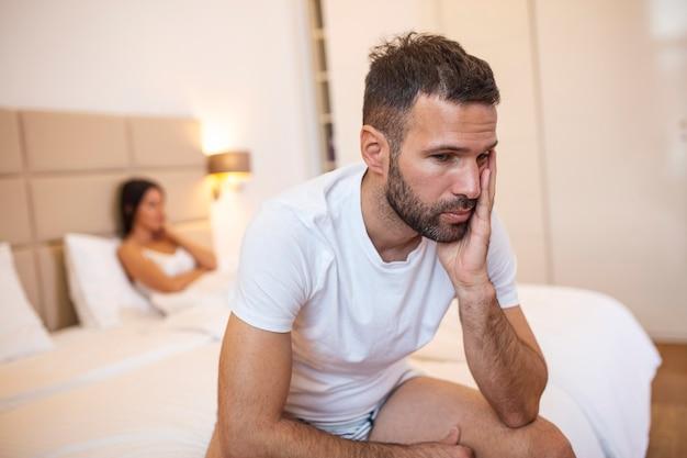 Linda garota e um homem frustrado, sentado na cama e sem olhar um para o outro.