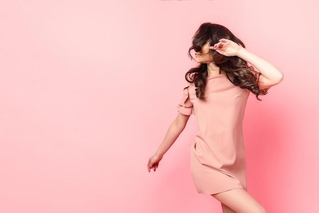 Linda garota elegante com cabelo longo cacheado em um vestido rosa no estúdio em um fundo rosa.