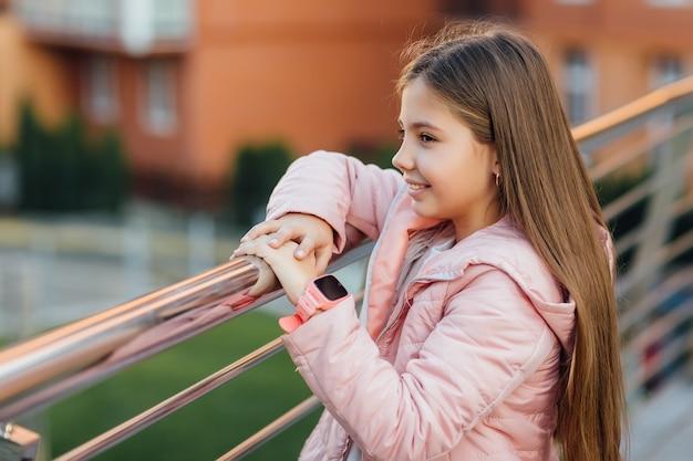 Linda garota elegante com relógio inteligente moderno caminhando depois da escola perto da cidade