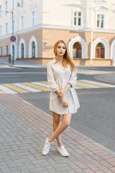 Linda garota elegante com um vestido e tênis em pé perto do prédio em um dia ensolarado de verão