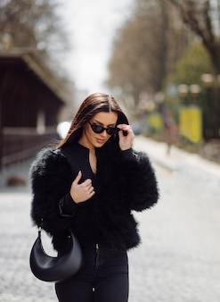 Linda garota elegante de cabelos castanhos em vestido preto ao ar livre. retrato de jovem atraente mulher elegante com cabelo comprido na primavera nas ruas da cidade.