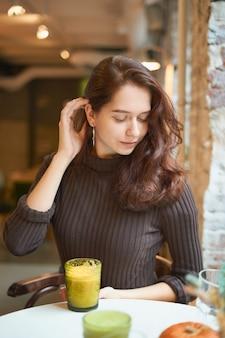 Linda garota elegante elegante elegante séria está sentado no café e bebendo suco saudável