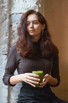 Linda garota elegante elegante séria elegante está sentado no café e bebendo suco verde