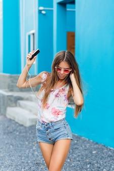 Linda garota elegante em fundo azul dança e ouve música em fones de ouvido no smartphone.