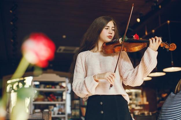 Linda garota elegante em pé em um café com violino