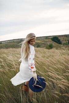Linda garota elegante em um campo de trigo outono