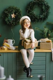 Linda garota elegante na cozinha decorada para o natal e ano novo. ela está segurando caixas de presente