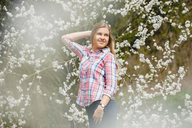 Linda garota em árvores floridas no início da primavera. sol brilhante e natureza