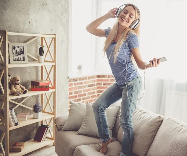 Linda garota em fones de ouvido está ouvindo música.