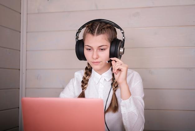 Linda garota em fones de ouvido na frente de um monitor de laptop. estudo online em casa