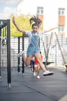 Linda garota em jeans pulando enquanto brincava com os amigos