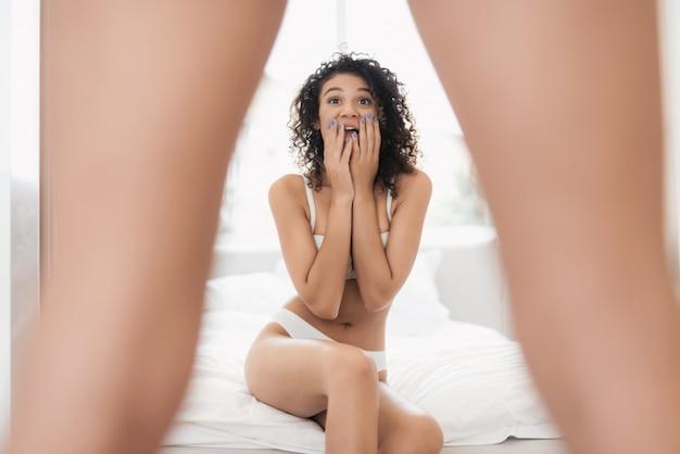 Linda garota em lingerie branca está sentado na cama