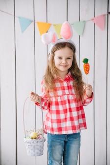 Linda garota em orelhas de coelho em pé com cesta de ovos de páscoa