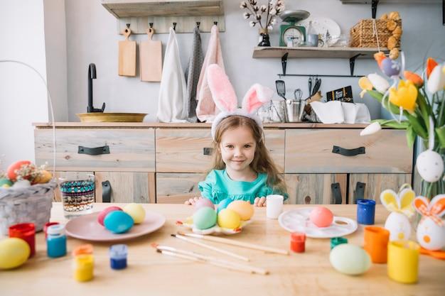 Linda garota em orelhas de coelho sentado à mesa com ovos de páscoa