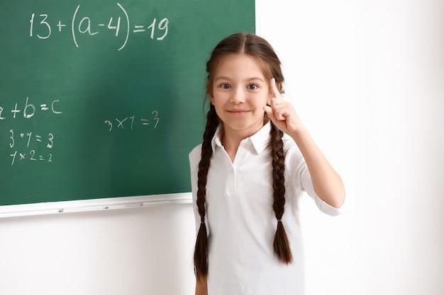 Linda garota em pé perto do quadro-negro na sala de aula