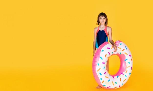 Linda garota em traje de banho azul com anel de borracha enorme inflado pulando em amarelo
