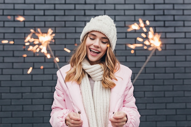 Linda garota em traje de inverno branco, comemorando os feriados. tiro ao ar livre de sorridente senhora romântica segurando luzes de bengala.