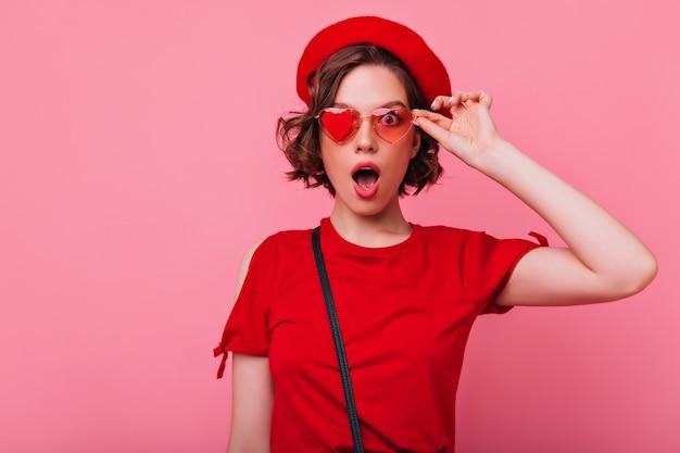 Linda garota em traje francês engraçado posando com expressão facial de surpresa. mulher espantada atraente com cabelos ondulados, tocando seus óculos de sol.