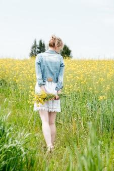 Linda garota em um campo amarelo. um buquê de flores de colza. dia quente e ensolarado de verão. um passeio ao ar livre. sorri e ri. gentil e envergonhado. volta, um buquê atrás.