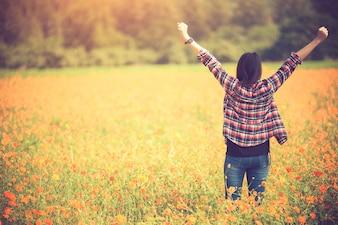 Linda garota em um campo de flor amarela ao pôr do sol. conceito de liberdade. Cor vintage