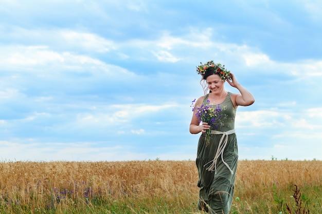 Linda garota em um campo de trigo com uma coroa na cabeça