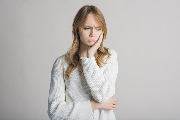 Linda garota em um fundo branco no estúdio está infeliz e chateada com algo