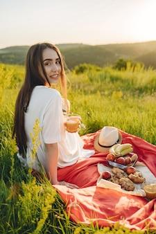 Linda garota em um piquenique no campo de verão