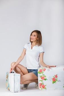 Linda garota em um shorts de t-shirt e denim divertido posando com uma mala
